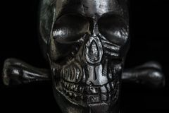 Metal skull on black background. Ominous glare on a metallic skull in the dark royalty free stock photography