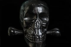 Metal skull on black background. Ominous glare on a metallic skull in the dark royalty free stock image