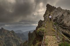 Ominous hiking in the mountains of Madeira. Couple of tourists hiking in the mountains of Madeira from Pico do Areeiro Arieiro to Pico Ruivo on a cloudy summer royalty free stock photo