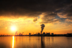 Ominous industry. Sunset view of the heavy industry with smoking chimneys in IJmuiden, the Netherlands. HDR stock photo