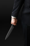 Ominous kitchen knife. An handsome businessman wearing a suit and a tie holding a big kitchen knife royalty free stock images
