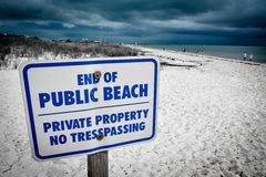 Ominous private beach. A sign on a Cape Cod beach warns the public to not enter the private section of the beach. The dramatic clouds effectively reinforces the stock photos