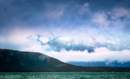 Ominous Skies Over Skagway, AK. Clouds and fog covering the snow-capped mountain peaks over the inlet at Skagway, Alaska royalty free stock images
