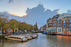 Ominous sky at the Amstel river. Beautiful cityscape view towards the Mint tower Munttoren with tourist canal boats at the Amstel river in Amsterdam, the Stock Image