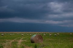 Ominous sky with Bales of Hay. Beautiful dark skies hover over bales of hay arranged artfully in a field stock photo