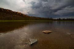 Ominous sky over the taiga river. The River Amga. Yakutia Royalty Free Stock Photo