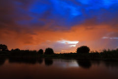 Ominous sky at the river. A dark colored ominous sky at the river at night in the Netherlands royalty free stock images