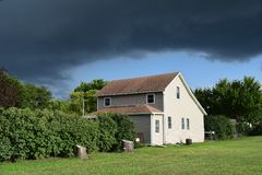 Dark cloud over small farmhouse rural Nebraska. Ominous storm cloud hanging over farm house bushes trees bright in contrasting sunlight, sliver of blue sky royalty free stock photography
