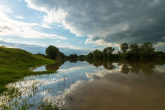 Ominous stormy sky over natural river. In spring stock images