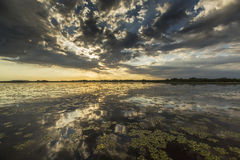 Ominous stormy sky reflection over natural lake. In the Danube Delta stock photo