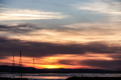 Ominous Sunset Skies over Alviso marina County Park, San Francisco Bay Area, California, USA. Intensive colored Sunset of hills and power transmission towers in royalty free stock photo