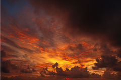 Ominous sunset , the sun paints the clouds red Royalty Free Stock Photo
