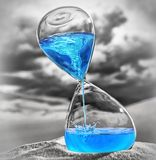 Ominous time. Hourglass with water spiraling inside on a desert royalty free stock photo