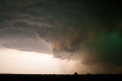 Ominous Wall Cloud. A large tornado-producing wall cloud glows green at the center of it's rotation Stock Image