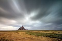 Ominous weather at Le Mont Saint-Michel. Beautiful view of historic landmark Le Mont Saint-Michel in Normandy, France, a famous UNESCO world heritage site and Stock Photo