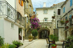Omisalj, Croatia. A town situated on the northern coast of the island of Krk. The street in the old town with buildings typical for the region - courtyard Royalty Free Stock Photo