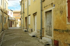 Omisalj, Croatia. A town situated on the northern coast of the island of Krk. The street in the old town with buildings typical for the region Royalty Free Stock Photography