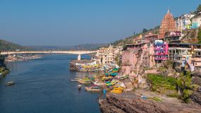 Omkareshwar cityscape, India, sacred hindu temple. Holy Narmada River, boats floating. Travel destination for tourists and pilgrim stock image