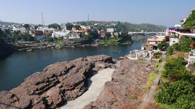 Omkareshwar cityscape, India, sacred hindu temple. Holy Narmada River, boats floating. Travel destination for tourists and pilgrim. S stock video footage