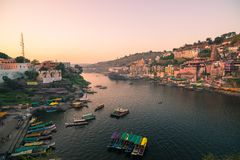 Omkareshwar cityscape, India, sacred hindu temple. Holy Narmada River, boats floating. Travel destination for tourists and pilgrim stock photography