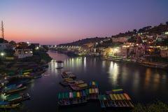 Omkareshwar cityscape på skymning, Indien, sakral hinduisk tempel Helig Narmada flod, sväva för fartyg Loppdestination för turist Royaltyfri Fotografi
