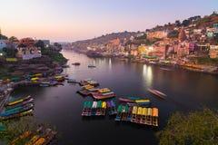 Omkareshwar cityscape på skymning, Indien, sakral hinduisk tempel Helig Narmada flod, sväva för fartyg Loppdestination för turist Royaltyfria Foton