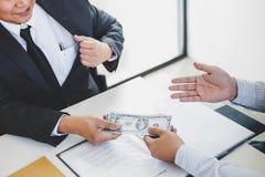 Omkoperij en corruptieconcept, steekpenning die in de vorm van dollarrekeningen, Zakenman geld geven terwijl het maken van overee royalty-vrije stock afbeeldingen