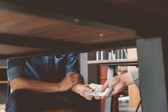 Omkoperij, Handen die geld overgaan onder lijst, Corruptie en omkoperij royalty-vrije stock afbeeldingen