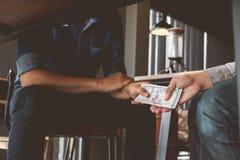 Omkoperij, Handen die geld overgaan onder lijst, Corruptie en omkoperij stock fotografie
