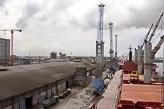 Omlastningterminalen för urladdning av cementlast förbi kusten sträcker på halsen En sikt av hytter med lastfartyg och vattenområ arkivbild