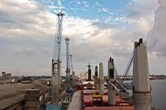 Omlastningterminalen för urladdning av cementlast förbi kusten sträcker på halsen En sikt av hytter med lastfartyg och vattenområ fotografering för bildbyråer
