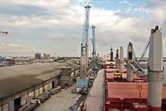 Omlastningterminalen för urladdning av cementlast förbi kusten sträcker på halsen En sikt av hytter med lastfartyg och vattenområ royaltyfri foto
