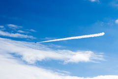 Ommercial airplane flying at high altitude leaving contrails against  dark blue sky. Stock Images