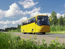 Omnibus turístico amarillo en la carretera y el paisaje rural Imagen de archivo