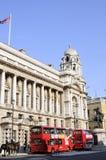 Omnibuses criculating delante del edificio histórico Fotografía de archivo libre de regalías