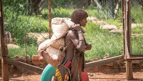 Unidentified woman from the tribe of Hamar carrying goods in the Omo Valley of Ethiopia stock photo