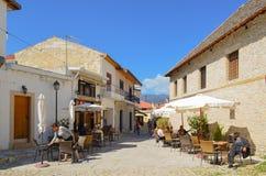 Omodos,塞浦路斯2015年5月15日 街道咖啡馆 一个年长人在椅子睡觉,女服务员清洗桌 免版税图库摄影