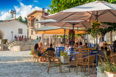 OMODOS,塞浦路斯- 2015年10月4日:与游人的街道咖啡馆的 免版税库存图片