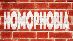 Omofobia scritta su un muro di mattoni Immagini Stock Libere da Diritti