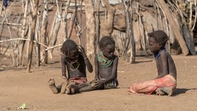 Unidentified girls from Dassanech tribe sitting on soil ground , Ethiopia stock photography