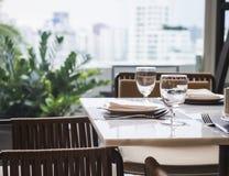 Łomotać Stołowego ustalonego Restauracyjnego wnętrze z ogródem vi i linią horyzontu Zdjęcia Stock