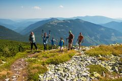 Сompany of joyful friends, travelers stands in the mountains. Сompany of joyful friends, travelers stands on the top in the mountains on a beautiful sunny day Stock Images