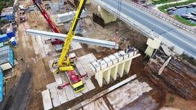 Område för brokonstruktion med enorma konkreta beems och kranar i förorter arkivfilmer