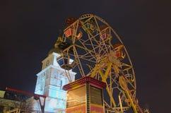 Område för underhållning för barn` s Pariserhjul för små ungar Klocka torn av helgonet Michael Cathedral på bakgrund Arkivfoto