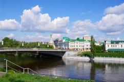Omsk, Rússia - 25 de maio de 2015: Arquitetura da cidade do verão com rio, ponte e o céu azul nas nuvens Fotografia de Stock