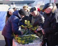Omsk Rosja, Marzec, - 07, 2015: Mężczyzna kupują gałąź kwitnące mimozy na rynku Zdjęcie Stock
