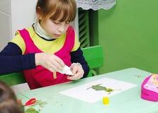 Omsk Rosja, Wrzesień, - 24, 2011: uczennica klei aplikację przy szkolnym biurkiem Zdjęcie Stock