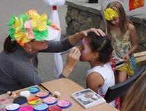 Omsk, Rusia - 3 de agosto de 2014: proceso de pintura de la cara al aire libre Imágenes de archivo libres de regalías