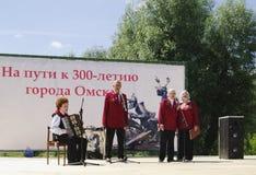 Omsk, Rusia - 12 de junio de 2015: el conjunto de veteranos canta la canción en escena al aire libre Foto de archivo libre de regalías