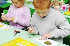 Omsk, Rusia - 24 de septiembre de 2011: colegiala y colegial en el escritorio de la escuela que hace el trabajo creativo de la ma Imagen de archivo libre de regalías